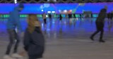 Defocused shot of many adults and children enjoying skating at illuminated skating-rink at night