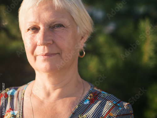 Portrait of beautiful aged woman in the park at sunset. Poster