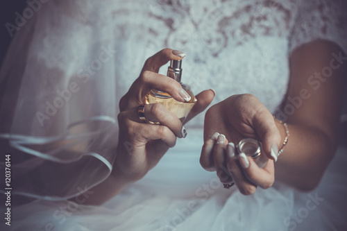 Poster bride applying perfume on her wrist
