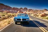 guy driving cool vintage car through nevada desert