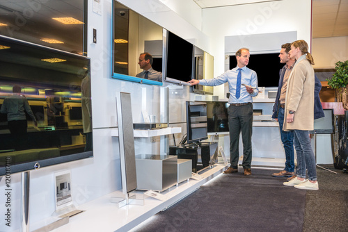 Salesman Showing Flat Screen Tv To Couple In Store