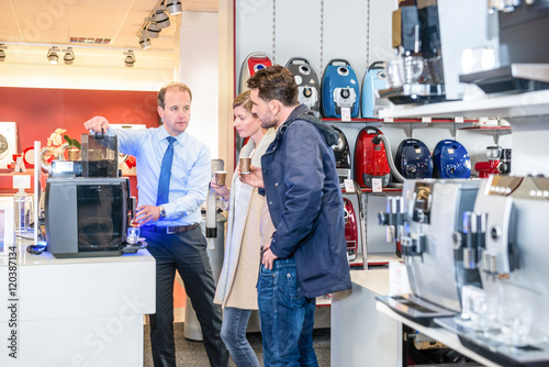 Salesman Showing Coffee Maker To Couple In Store