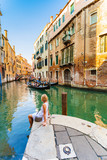 Woman sits near a canal and admires gondolas and architecture of Venice. Italy.