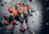 Male and female climbing on an indoor climbing wall.