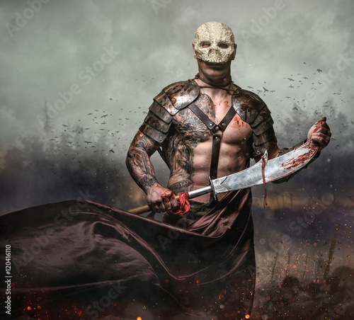Male in the skull mask holds sword in the dust batterfield backg