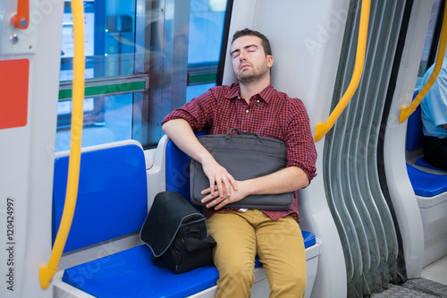 Tired commuter sleeping on the metro seat