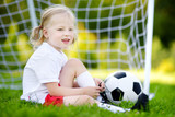 Cute little soccer player having fun playing a soccer game