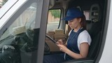 Delivery woman in blue uniform counting packages while sitting in car and making notes in application form