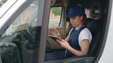 Delivery woman in uniform counting packages while sitting in car and using digital tablet