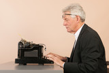 Senior man with antique typewriter