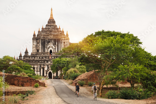 Tourists riding bicycle near pagodas in Bagan on sunset Poster