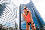 Portrait of a young sports woman outdoors on the modern skyscrapers background. Healthy lifestyle in Milan city.