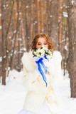 Bride with the flower bouquet in winter forest