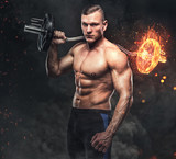 Athletic male holds the burning barbell.