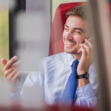 Picture of businessman in train making deal by phone call