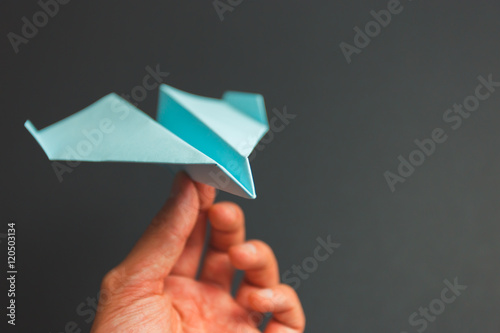 Blue paper airplane origami in hand