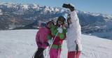 Teenage girls take a selfie on ski slope