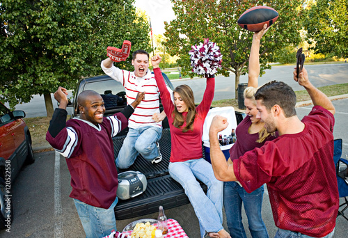 Tailgating: Group Of Friends Cheering While Listening To Footbal