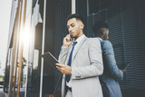 Serious businessman wearing grey suit and talking on his smartphone outside and using modern digital tablet while working at modern office, professional manager with devices, flare light