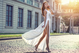 Beautifilul elegant woman in long white flattering dress walking