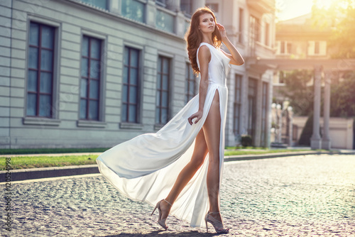 Beautifilul elegant woman in long white flattering dress walking Poster