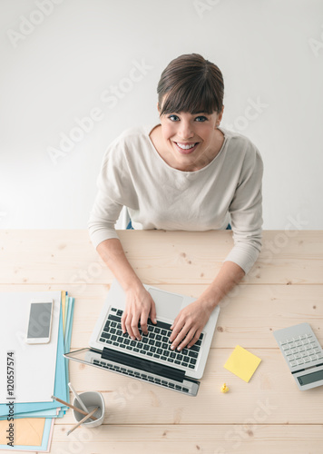 Smiling businesswoman in the office - 120557574