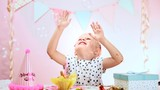 Playful kid catching falling bubbles in decorated room at home. Concept of excitement and happiness.