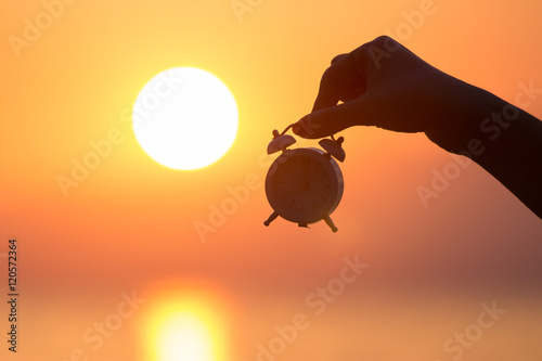 Silhouette of female hand holding small alarm clock and sunrise over sea in the background Poster