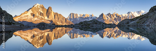 Poster Panorama of Alps mountain range, sunset lights, reflection in lake