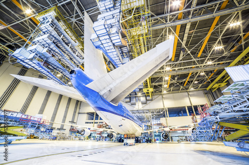 Refurbishment of an airplane in a hangar. Poster