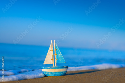 toy sailboat at the seashore during sunrise Poster