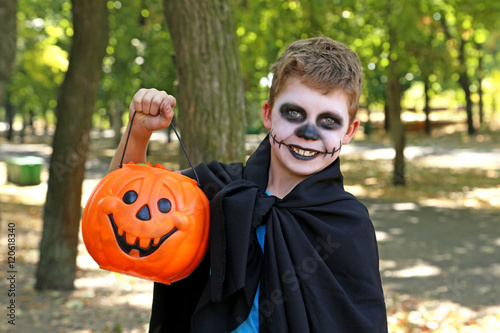 Poster Little boy in halloween costume with basket for candies in the p