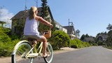 Woman riding bicycle in coastal vacation community