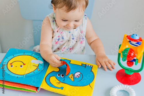 small child playing with soft book