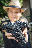 Teenage boy with bunch of grapes in hands, vintage theme