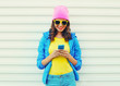 Fashion happy cool smiling girl using smartphone in colorful clo