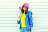 Portrait fashion pretty cool smiling woman with lollipop in colo
