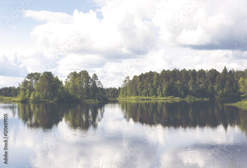 Beautiful summer day at the lake. Water makes beautiful reflection. Image has a vintage effect applied. - 120689105