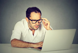 Worried businessman working on laptop computer