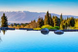 Beautiful landscape view of the lake, trees and snow mountains peaks on the background