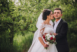 couple in wedding attire with a bouquet of flowers and greenery is in the hands against the backdrop of the garden at sunset, the bride and groom