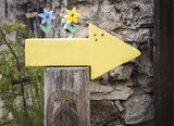 yellow arrow and a shell carved in a wooden log on the way to Santiago with space to write your own message