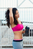 Sporty beautiful woman taking an urban fitness workout rest for drinking water.