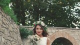 Happy bride in wreath posing with wedding bouquet near castle. Slowly