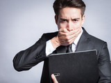 Keeping a secret.  Businessman with hand over mouth.  - 120765139