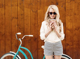Young sexy blonde girl with long hair in sunglasses standing near vintage green bicycle and holding a cup of coffee have fun and good mood looking in camera and smiling, warm, tonning