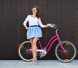 Trendy Fashionable Girl with Vintage Bike on Wooden Background. Toned Photo. Modern Youth Lifestyle Concept.