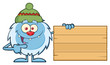 Cute Little Yeti Cartoon Mascot Character With Hat Pointing To A Wooden Blank Sign