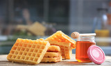 Waffles and honey on a wooden table