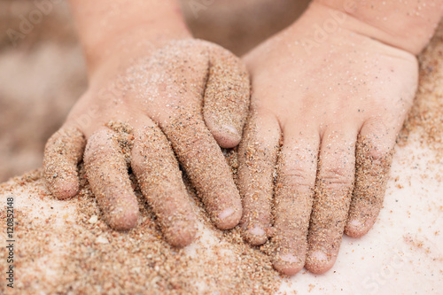 Hands in the sand on the beach Poster